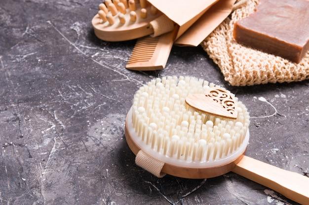Escova redonda de madeira para massagem a seco contra celulite em uma superfície preta, estilo de vida ecologicamente correto, sabonete doméstico, pano de malha tricotado