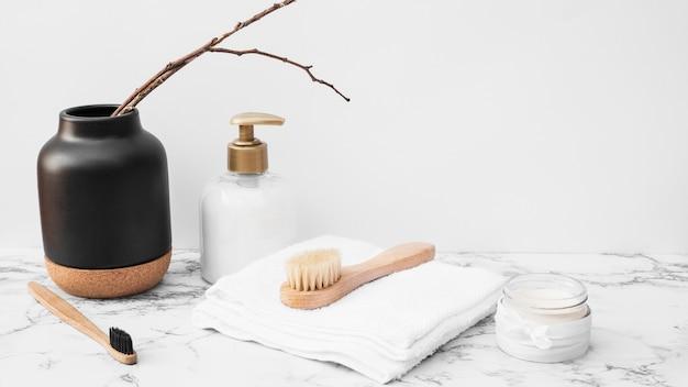 Escova; toalha; creme hidratante e frasco cosmético na superfície de mármore