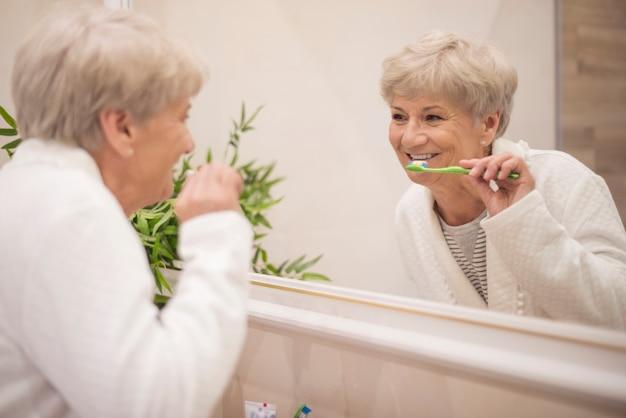Escovando os dentes em frente ao espelho
