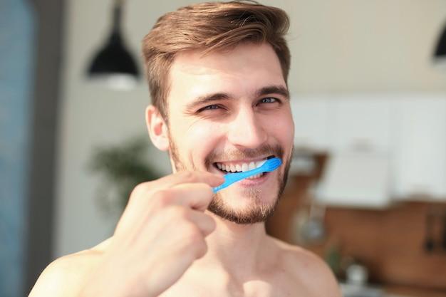 Escovar os dentes pela manhã. homem de barba jovem bonito escovando os dentes e sorrindo.