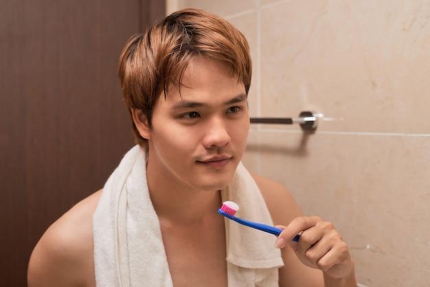 Escovar os dentes pela manhã. jovem atraente escovando os dentes com uma escova de dentes e se olhando no espelho