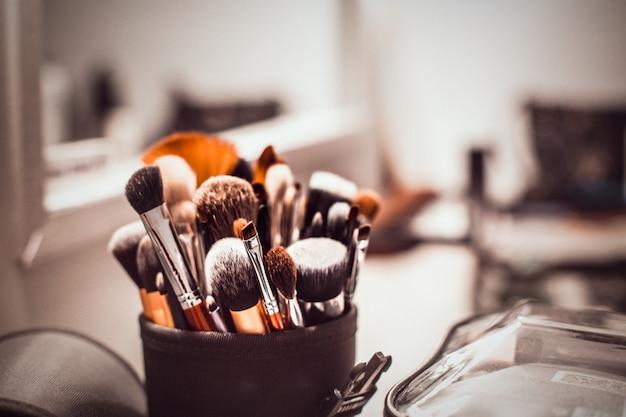 Escovas da composição-composição do artista do maquilhador e produtos cosméticos na tabela com um espelho.