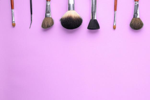 Escovas da composição em um fundo cor-de-rosa.