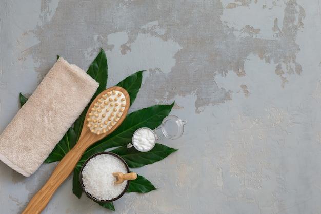 Escovas de bambu de tratamento de spa corpo com toalha de banho, sal e creme em fundo verde folha tropical