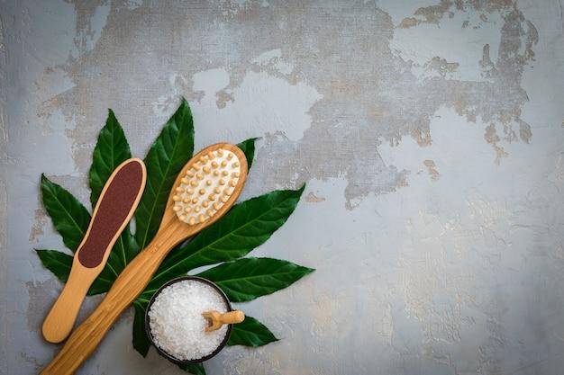 Escovas de bambu de tratamento de spa de corpo com sal de banho em fundo verde folha tropical