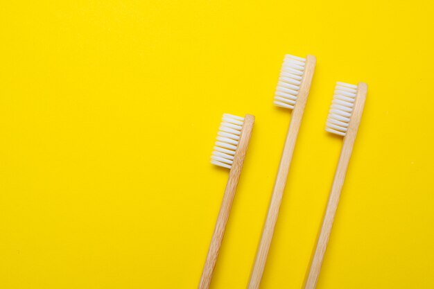 Escovas de bambu em uma superfície amarela
