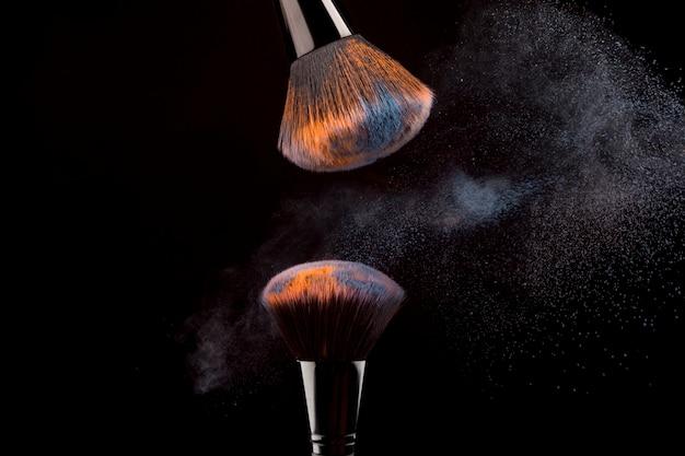 Escovas de cosméticos com névoa de pó em fundo escuro