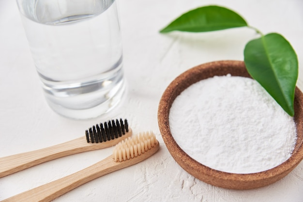 Escovas de dente de bambu, bicarbonato de sódio e copo d'água