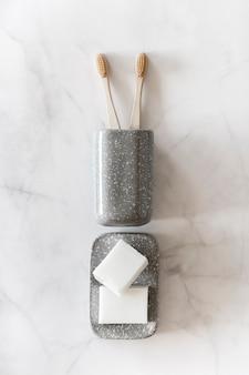 Escovas de dente de bambu biodegradáveis e sabonete natural em fundo de mármore