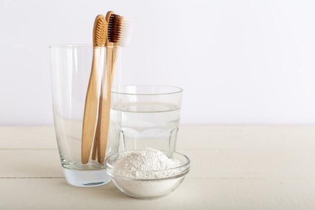 Escovas de dente de bambu, copo d'água, dentifrício em pó no fundo branco. resíduos zero