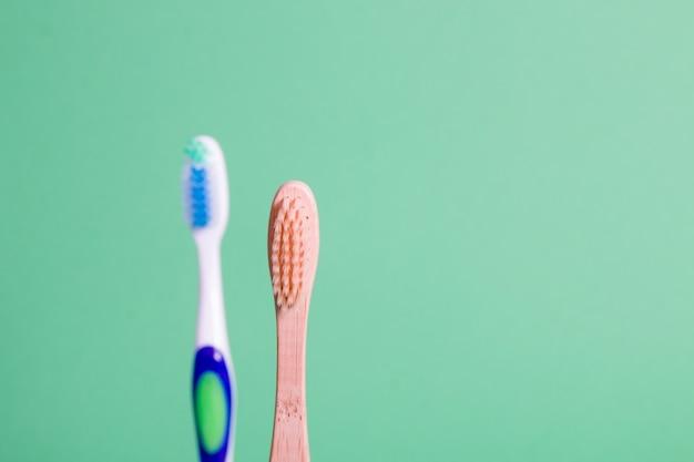 Escovas de dente de bambu e plástico em um fundo verde, conceito de estilo de vida ecológico