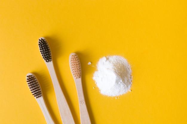 Escovas de dente de bambu e refrigerante em um fundo amarelo coloque copie a vista de cima