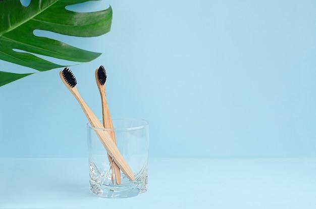 Escovas de dente de bambu em um copo e folha monstera com espaço de cópia