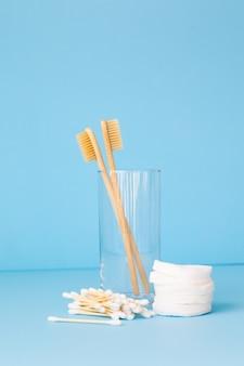 Escovas de dente de bambu em um fundo azul em um vidro produtos de higiene pessoal ecológicos para pessoas
