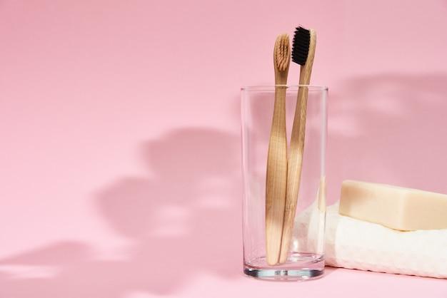 Escovas de dente de bambu em vidro e sombras de folhas em rosa