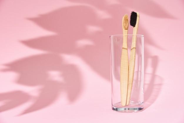 Escovas de dente de bambu em vidro e sombras de folhas
