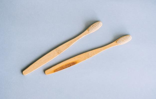 Escovas de dente de bambu fazendo com materiais naturais, isoladas em um fundo cinza, close-up.