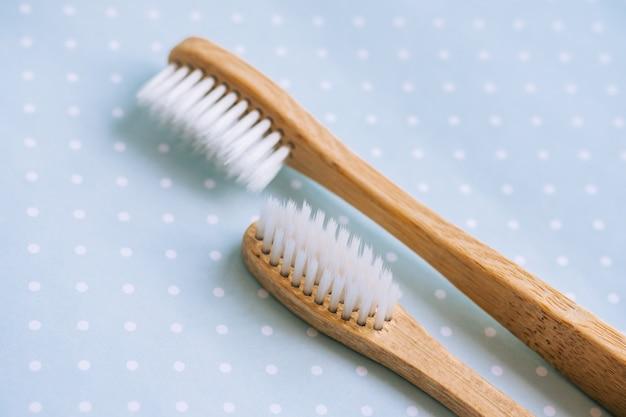 Escovas de dente de bambu fazendo com materiais naturais, isoladas em um fundo verde, close-up.