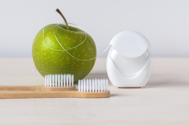 Escovas de dente de bambu, maçã verde e fio dental em fundo branco - rotina de atendimento odontológico para manter os dentes saudáveis