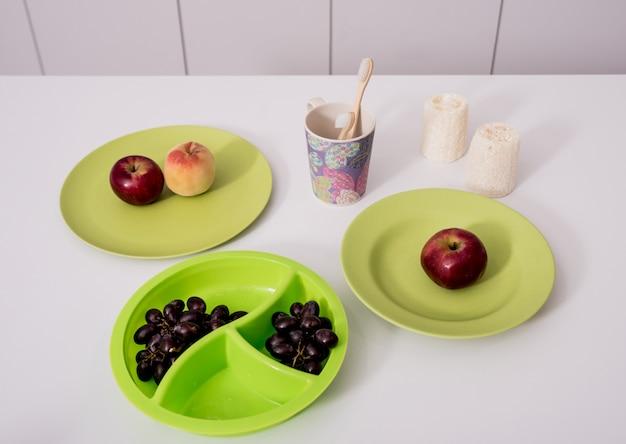 Escovas de dente de bambu, panos, copos e pratos na mesa branca na cozinha. desperdício zero