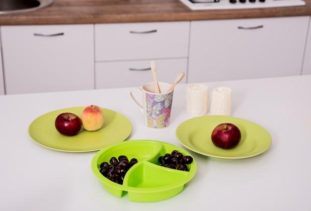 Escovas de dente de bambu, panos, copos e pratos na mesa branca na cozinha