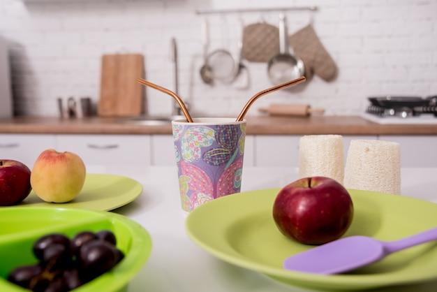 Escovas de dente de bambu, panos, copos e pratos na mesa branca