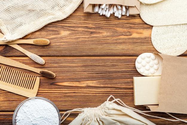 Escovas de dente de bambu, sabão em pó, toalhetes de algodão cotonetes varas de madeira com fundo de madeira