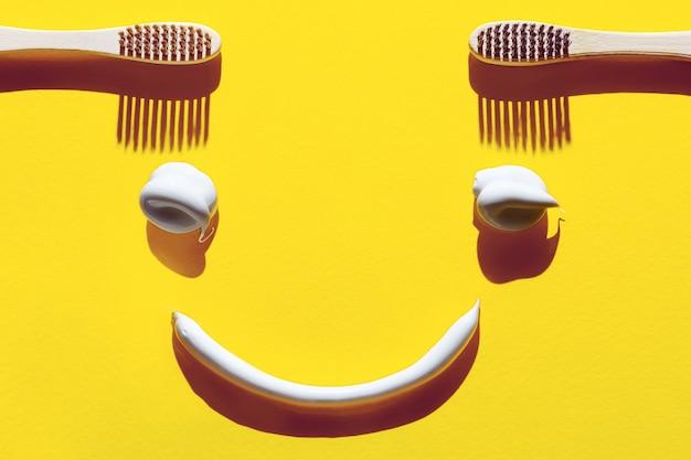 Escovas de dente de madeira e macarrão em um fundo amarelo. conceito dental na forma de uma cara engraçada.