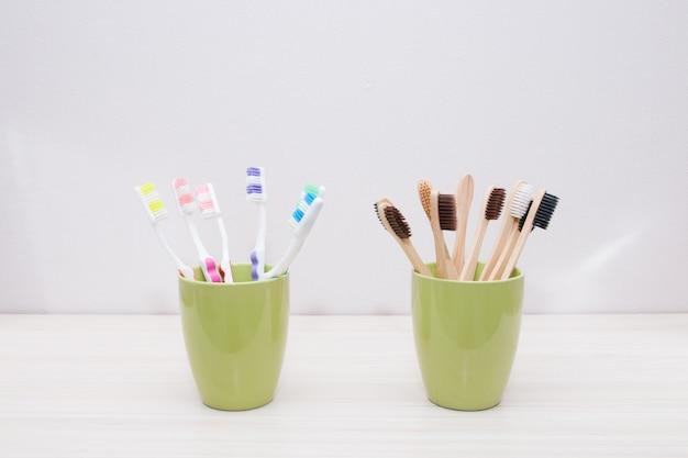Escovas de dente de plástico e bambu em copos verdes, fundo claro, espaço de cópia, conceito de material ecológico