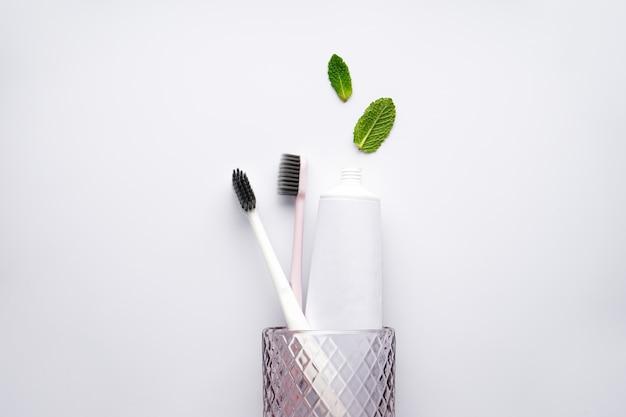 Escovas de dente e creme dental em um copo sobre fundo branco com folhas de hortelã