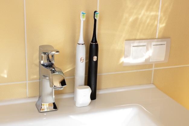 Escovas de dente elétricas interativas inteligentes na pia do banheiro