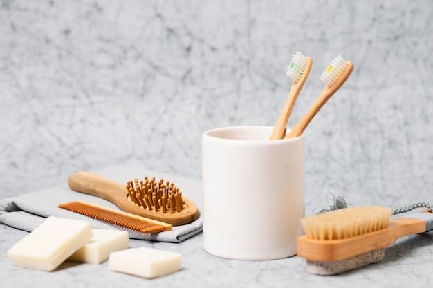 Escovas de dente em copo e escova de cabelo natural