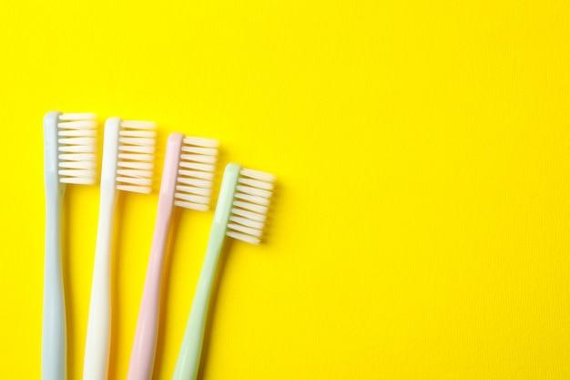 Escovas de dente em fundo amarelo, espaço para texto