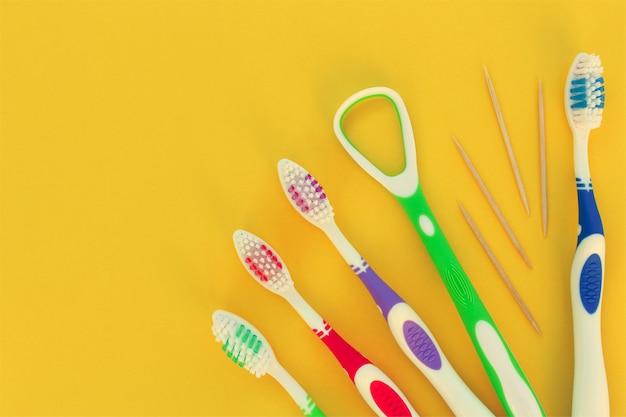 Escovas de dente, palito, raspador de língua em um amarelo