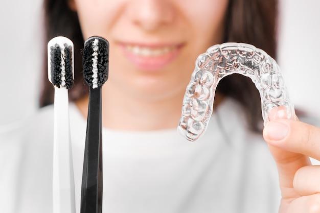 Escovas de dente preto e branco e alinhador removível invisível nas mãos da mulher