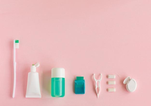 Escovas de dentes, creme dental, enxágüe e chicletes em rosa
