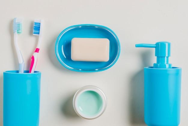 Escovas de dentes; creme; dispensador de sabão e sabão em recipiente azul com creme em fundo branco
