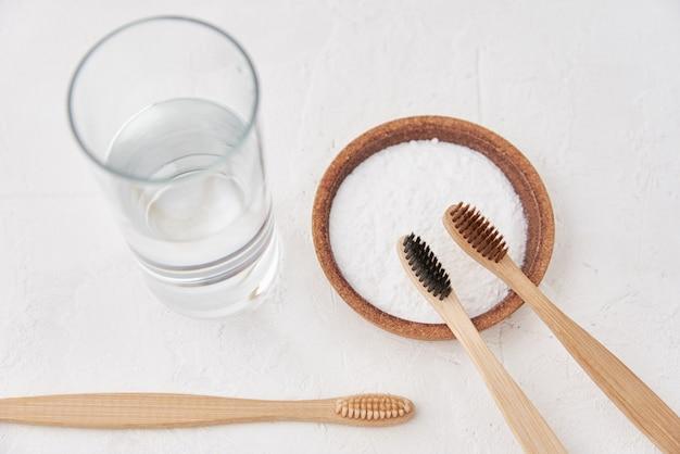 Escovas de dentes de bambu, bicarbonato de sódio e copo de água em um fundo branco. escovas de dentes ecológicas, conceito de desperdício zero