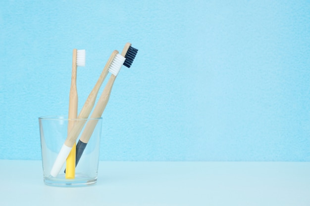 Escovas de dentes de bambu de cores diferentes em um vidro transparente sobre um fundo azul com um espaço de cópia. zero conceito de resíduos