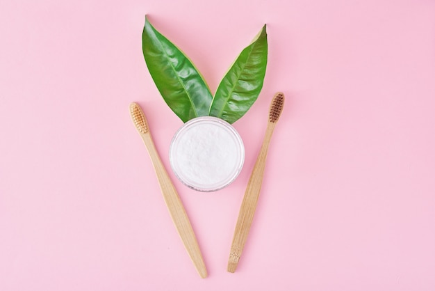 Escovas de dentes de bambu de madeira com bicarbonato de sódio em pó no frasco de vidro e folhas verdes em um fundo rosa. saúde dos dentes e manter o conceito de boca