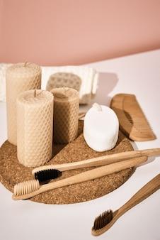 Escovas de dentes de bambu e velas em fundo rosa. reutilizar produtos naturais