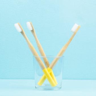 Escovas de dentes de bambu eco-friendly em um vidro transparente sobre um fundo azul
