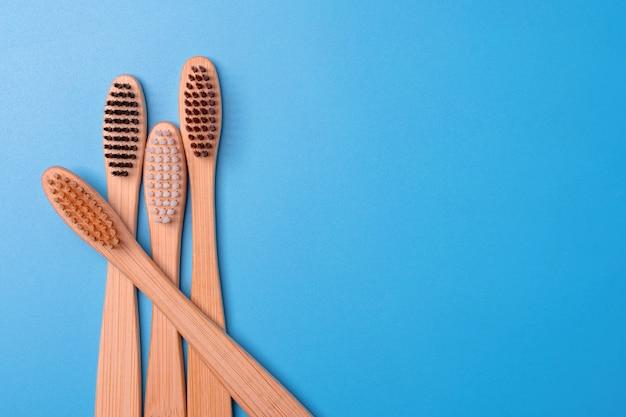 Escovas de dentes de bambu em fundo azul. higiene bucal diária ecológica, cuidados com os dentes e saúde. produtos de limpeza para a boca. conceito de atendimento odontológico.