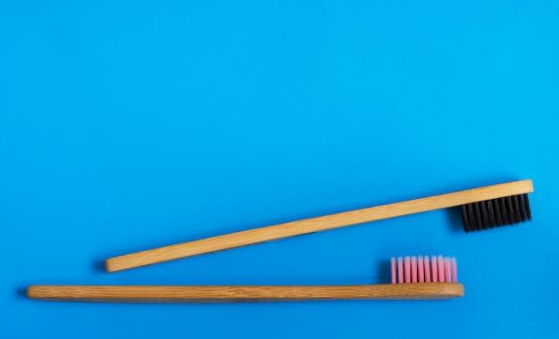 Escovas de dentes de bambu naturais de eco sobre fundo azul. zero resíduos plana leigos 12