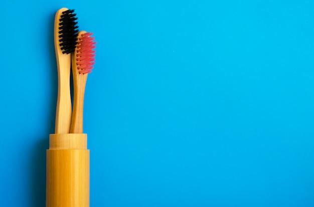 Escovas de dentes de bambu naturais de eco sobre fundo azul. zero resíduos plana leigos 14