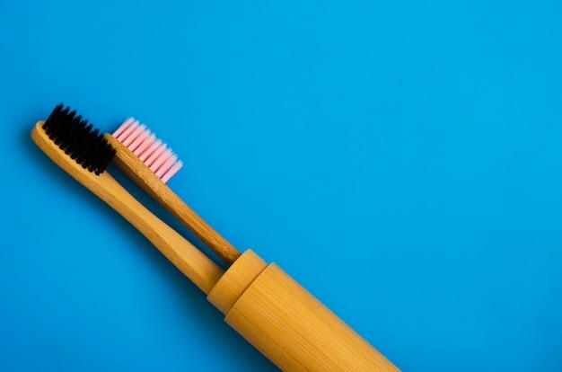 Escovas de dentes de bambu naturais de eco sobre fundo azul. zero resíduos plana leigos 17