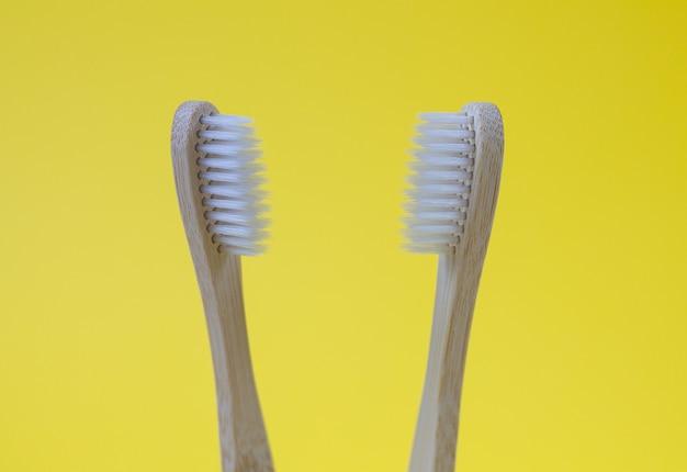 Escovas de dentes de madeira de bambu na moda isoladas em fundo amarelo