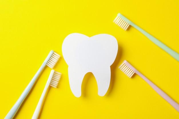 Escovas de dentes e dente na superfície amarela