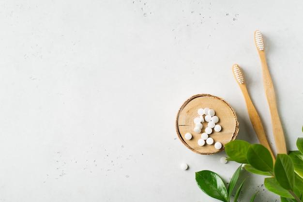 Escovas de dentes ecológicas de madeira e pastilha de dentífrico no fundo branco