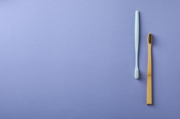 Escovas de dentes ecológicas e de plástico em fundo violeta